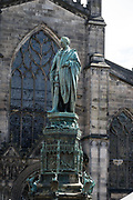 "Duke of Buccleuch (Walter Scott) statue by Boehm (1888) in front St Giles' Cathedral, Edinburgh, Scotland, UK, Europe. ""This statue of Walter Francis Montagu Douglas Scott (1806-1884), the 5th Duke of Buccleuch and the 7th Duke of Queensbury K.G. was unveiled in Parliament Square on 7th February 1888. The regal bronze cast depicts a standing figure wearing Order of the Garter robes. The design for the main part of the statue was by J. Edgar Boehm. Various other artists were responsible for the panels which illustrate episodes in the Duke's life and family history. The battle scenes are particularly graphic."""