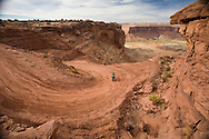 A motorcyclist touring on Mineral Bottom Road below the red sandstone escarpments in Canyonlands National Park, Utah