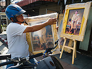 01 DECEMBER 2016 - BANGKOK, THAILAND: A man gets on his motorcycle with a portrait of HRH Crown Prince Maha Vajiralongkorn, who will soon be the new King of Thailand. Thailand's parliamentary body, the National Legislative Assembly, invited HRH Crown Prince Maha Vajiralongkorn to be king following the death of the Crown Prince's father, Bhumibol Adulyadej, the Late King of Thailand. The invitation marked the formal beginning of the process of naming the new King, although Crown Prince Vajiralongkorn was the heir apparent and Bhumibol's appointed successor. Shops that sell royal paraphernalia are now selling new portraits of  Crown Prince Vajiralongkorn which will be displayed alongside portraits of his late father. King Bhumipol died on Oct 13.      PHOTO BY JACK KURTZ