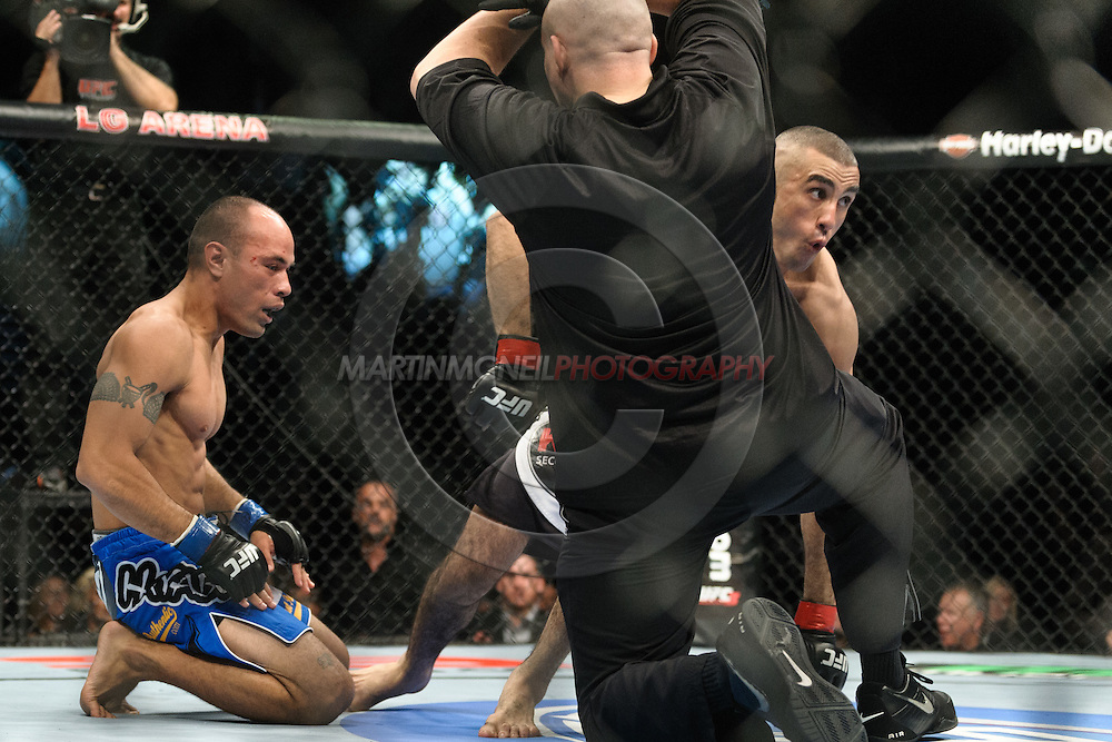 """BIRMINGHAM, ENGLAND, NOVEMBER 5, 2012: Edward Faaloloto (left) kneels on the canvas after submitting to a guillotine choke from Terry Etim during """"UFC 138: Munoz vs. Leben"""" inside the National Indoor Arena in Birmingham, United Kingdom"""