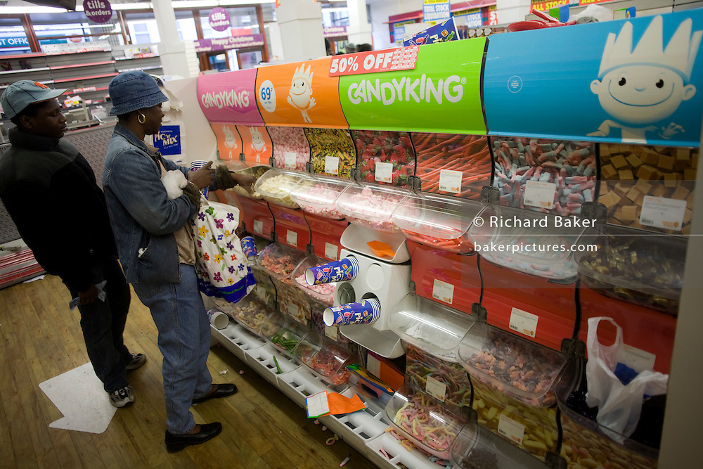 The last customers help themselves to sweets at the Pic n Mix dispenser in the closing Camberwell branch of Woolworths.