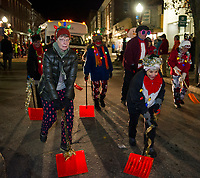 """The Taylor Community """"Shovel Brigade"""" led by Larry Frates works their way down Main Street during the """"Light Up Laconia"""" Holiday Parade on Sunday evening.  (Karen Bobotas/for the Laconia Daily Sun)"""