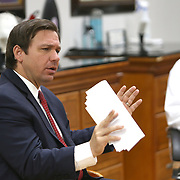 Florida Governor Ron DeSantis discusses with Orange County Mayor Jerry Demings on how to safely reopen Florida salons with small business owners during a roundtable at OhSoooJazzy Hair Salon in Orlando, Florida on Saturday, May 2, 2020. (Alex Menendez via AP)