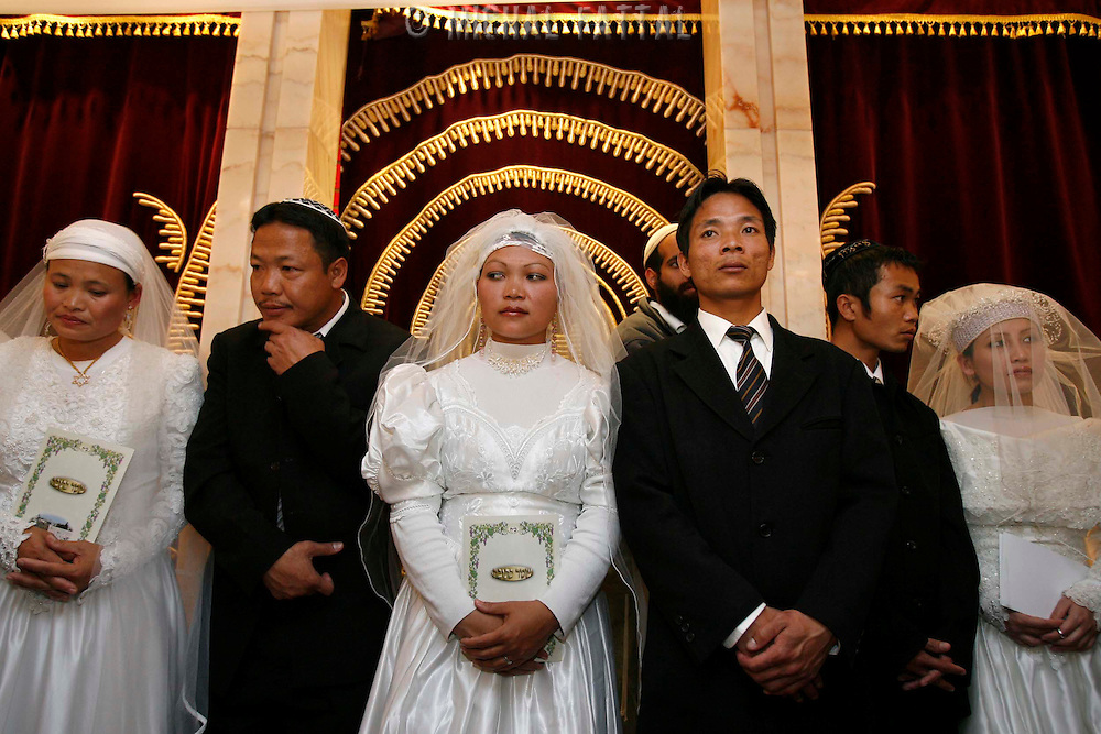 18 couples of Jewish immigrants from India, member of the 'Bnei HaMenashe' community, stand under the canopy as they get married in a shared wedding ceremony at the The Great Synagogue in Jerusalem, March 02, 2008. For the last 50 years Bnei Hamenashe seek their roots in Judaism as one of the lost tribes of Israel. Today 7000 Bnei Hamenashe in the States of Manipur and Mizoram in North India live full Jewish lives. Those who immigrate to Israel undergo Orthodox conversion in the framework of which they have to remarry according to Jewish Law...Photo by Michal Fattal..... *** Local Caption *** ..
