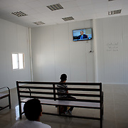 August 09, 2013 - Zarqa, Jordan: Syrian refugees watch a news channel at the communal television room of Mrigb Al-Fuhud refugee camp, also known as Emirates-Jordanian camp, 20 kilometres east of the Jordanian city of Zarqa.<br /> The 10 million USD camp, which has 750 caravans, a hospital, and a school and can take up to four thousand people, first opened in April 2013 and was paid for by the United Arab Emirates. Work is underway to house a total of 20 thousand by the end of the year.<br /> In contrast with the two other camps in the area, Mrigb Al-Fuhud as been classified by many as a 'five star' camp due to impressive housing facilities provided to the refugees. (Paulo Nunes dos Santos/Al Jazeera)