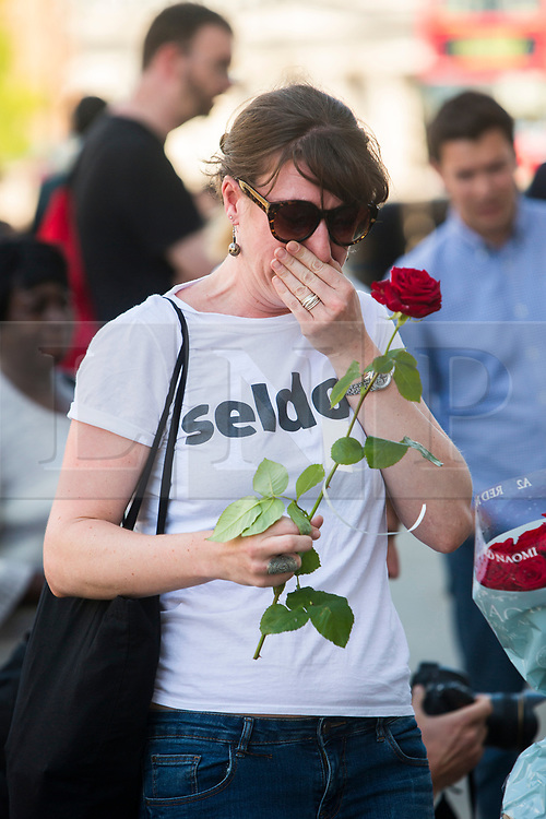 © Licensed to London News Pictures. 26/04/2016. London, UK.  A woman reacts after being handed a rose by members of the 1000RosesLondon group on London Bridge a week after a terror attack killed eight people. The group hopes to promote love and solidarity. Photo credit: Cliff Hide/LNP