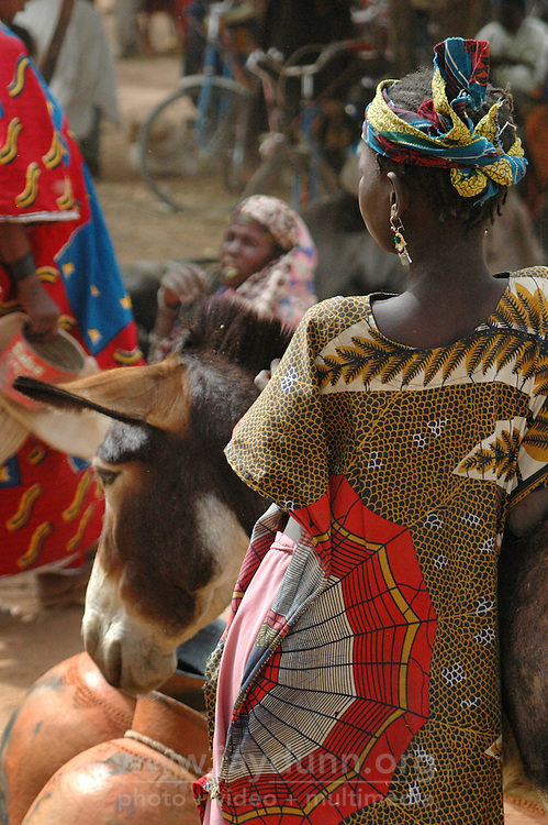 BURKINA FASO, Gorom-Gorom, 2007. A Bella woman watches over her handmade pots at Gorom-Gorom's regional market.