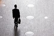 silhouetted business man with briefcase walking alone