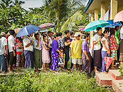 08 NOVEMBER 2015 - YANGON, MYANMAR: People stand in line to get into their polling place in North Okkalapa, a township outside of central Yangon. The citizens of Myanmar went to the polls Sunday to vote in the most democratic elections since 1990. The National League for Democracy, (NLD) the party of Aung San Suu Kyi is widely expected to get the most votes in the election, but it is not certain if they will get enough votes to secure an outright victory. The polls opened at 6AM. In Yangon, some voters started lining up at 4AM and lines were reported to long in many polling stations in Myanmar's largest city.      PHOTO BY JACK KURTZ