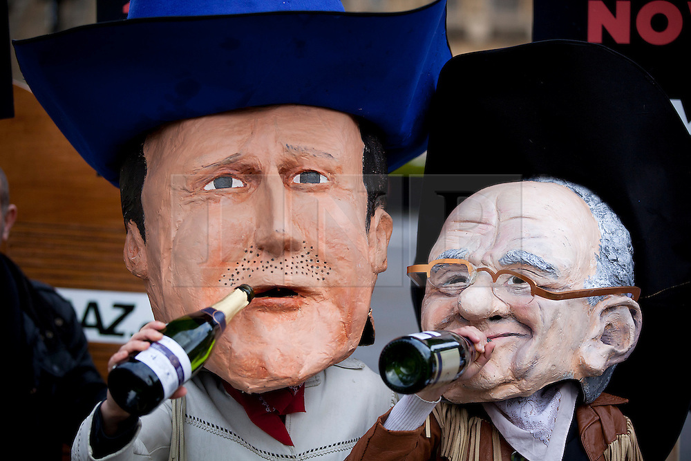 © Licensed to London News Pictures. 03/12/2012. London, UK. Wearing masks representing David Cameron and Rupert Murdoch, members of activist group Avaaz protest outside Parliament in London today (03/12/12). The group, who say they are backed by 28,000 people, want to see a 20% cap imposed on the amount of media that any one person or company can own. Photo credit: Matt Cetti-Roberts/LNP