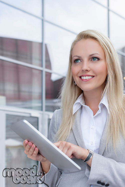 Happy businesswoman using digital tablet while looking away against office building