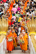 """22 JULY 2013 - PHRA PHUTTHABAT, THAILAND: Buddhist monks climb the stairway to the Mondop (chapel that houses the footprint) before the Tak Bat Dok Mai at Wat Phra Phutthabat in Saraburi province of Thailand, Monday, July 22. Wat Phra Phutthabat is famous for the way it marks the beginning of Vassa, the three-month annual retreat observed by Theravada monks and nuns. The temple is highly revered in Thailand because it houses a footstep of the Buddha. On the first day of Vassa (or Buddhist Lent) people come to the temple to """"make merit"""" and present the monks there with dancing lady ginger flowers, which only bloom in the weeks leading up Vassa. They also present monks with candles and wash their feet. During Vassa, monks and nuns remain inside monasteries and temple grounds, devoting their time to intensive meditation and study. Laypeople support the monastic sangha by bringing food, candles and other offerings to temples. Laypeople also often observe Vassa by giving up something, such as smoking or eating meat. For this reason, westerners sometimes call Vassa the """"Buddhist Lent.""""       PHOTO BY JACK KURTZ"""
