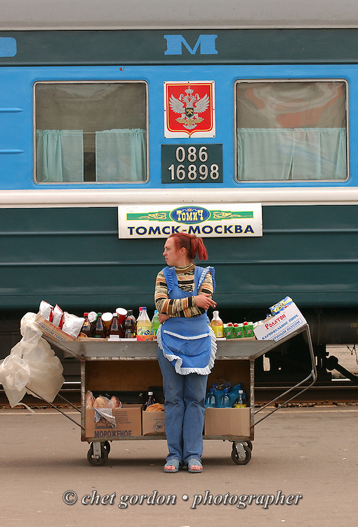 A woman sells food products on the platform in front of a Moscow-to-Tomsk, Siberia train car during a brief stop along the Trans-Siberian Railway in Kirov, Russian Federation on June 10, 2005.
