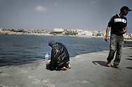 ITALY. Lampedusa: A tunisian migrant prays in the port of Lampedusa on March 26, 2011. Copyright Christian Minelli.