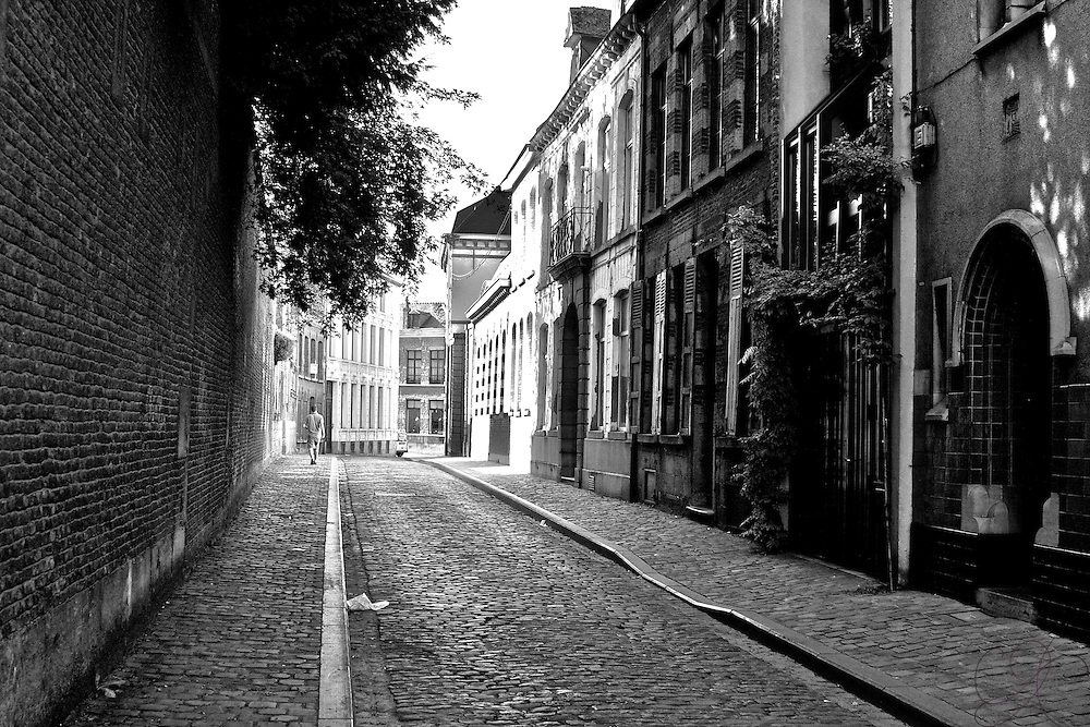 A man walks down Rue des 4 Fils Aymon - 4 Aymon Sons Street in downtown Mons. Much of the city's downtown still has old cobblestone roads and walkways, giving the city a very old world feel/ Black and White version