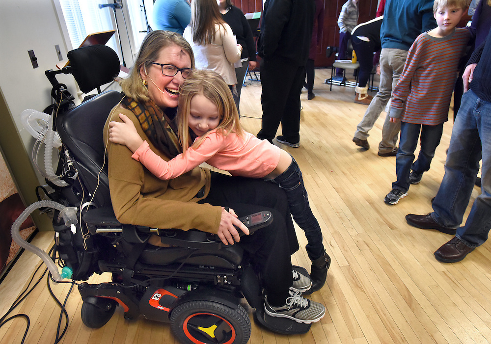 Mara Lavitt -- Special to the Hartford Courant<br /> February 14, 2016, Glastonbury<br /> Amyotrophic Lateral Sclerosis (ALS) forced Nancy Butler of Marlborough, left, to step down as pastor of the Riverfront Family Church in Glastonbury during the Sunday service. After the service she got a hug from Camryn Hunt age 7 of South Windsor. Ashes that were applied during the service can be seen on her forehead.