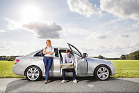 Full length of young woman looking away while man reading map in car at countryside