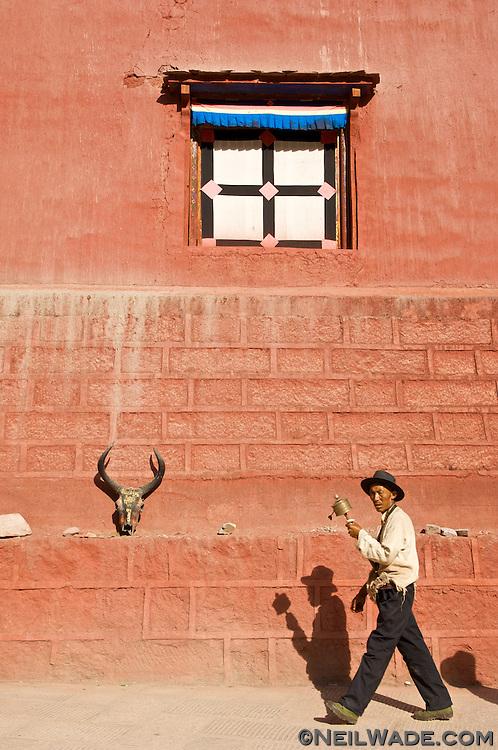 A Tibetan man walks a kora around the Barkhang (Parkhang) Printing Press in Dege, Tibet.
