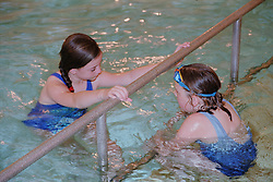 Young girl with learning disabilities holding onto bar in public swimming pool talking to young girl with complex congenital heart disease,