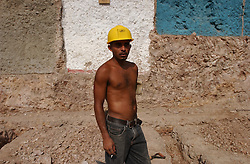 """Nelson Blanco pauses while working on a government project to build houses in """"El Cementerio"""", an area which has one of the many slums in Caracas.  Blanco, like all the other workers on the project, lives in the community.  Many of the houses in the community are currently made of tin and cardboard."""