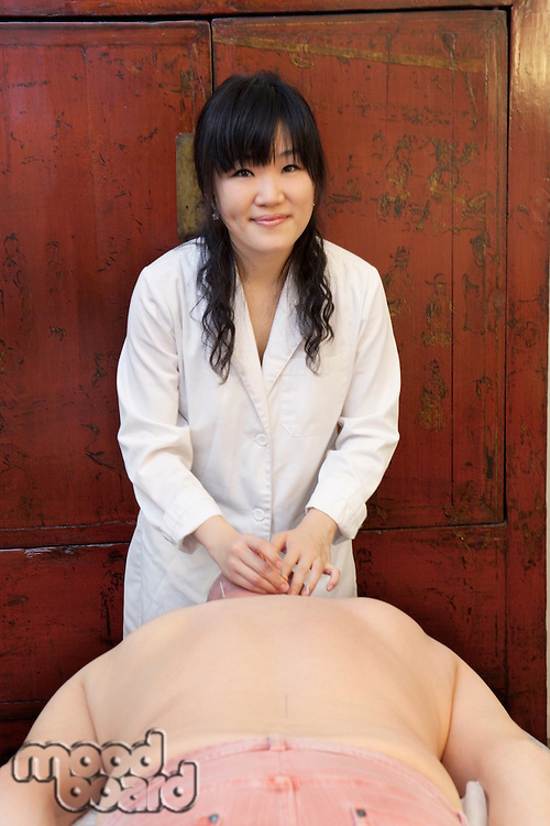 Portrait of a confident female acupuncturist with senior man lying