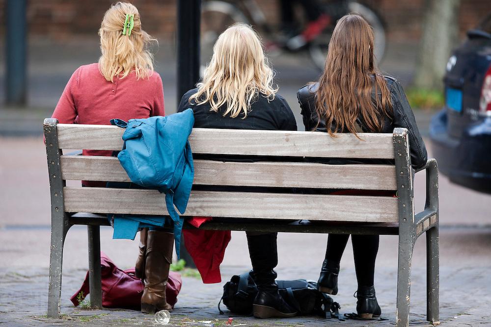 Drie meisjes zitten op een bankje op het Janskerkhof in Utrecht.<br /> <br /> Three girls are sitting on a bench.