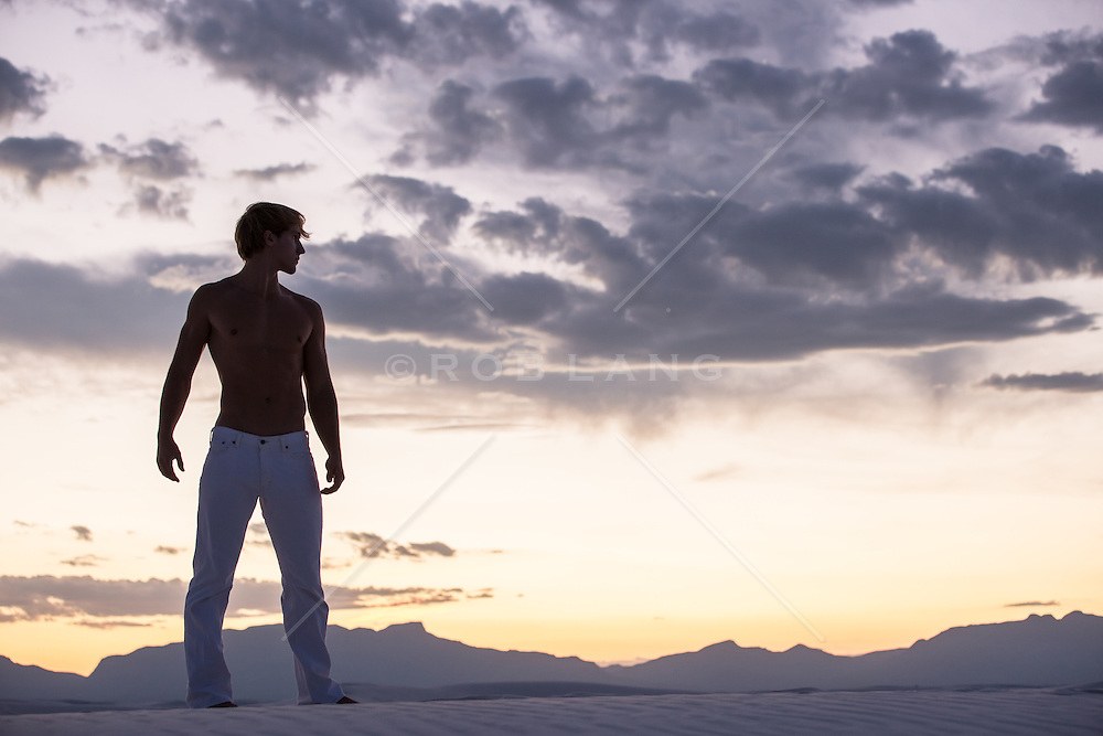 shirtless man in White Sands New Mexico at sunset
