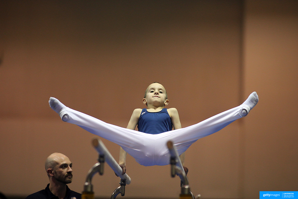 A young gymnasts in action on the parallel bars watched by his coach during the 21st American Invitational 2014 competition at the XL Centre. Hartford, Connecticut, USA. USA. 31st January 2014. Photo Tim Clayton