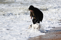 © Licensed to London News Pictures. 05/03/2015. Brighton, UK. A woman plays in the sea with her dog in Brighton today Thursday March 5th 2015. Photo credit : Hugo Michiels/LNP