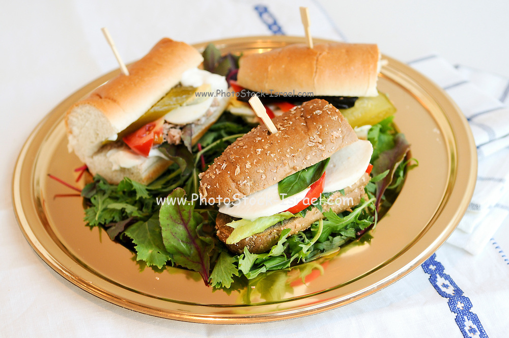 A plate of sandwich rolls on a layer of lettuce