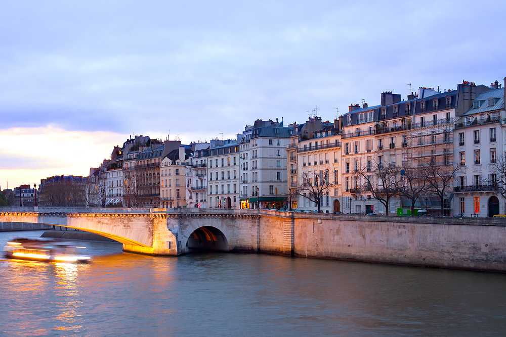Boat on the Seine River passing by Pont de la Tournelle bridge in front of Ile Saint Louis, Paris, France