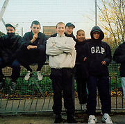 A group of bored lads sitting and standing by a wire fence