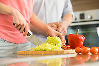 Midsection of woman chopping vegetables in kitchen with man standing in background