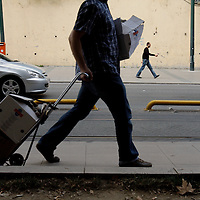 A man carries boxes along a sidewalk in Istanbul, Turkey.
