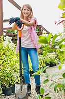 Portrait of mature gardener smiling while leaning on shovel