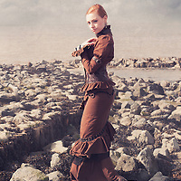 Young woman in a victorian dress standing alone outdoors beside the sea