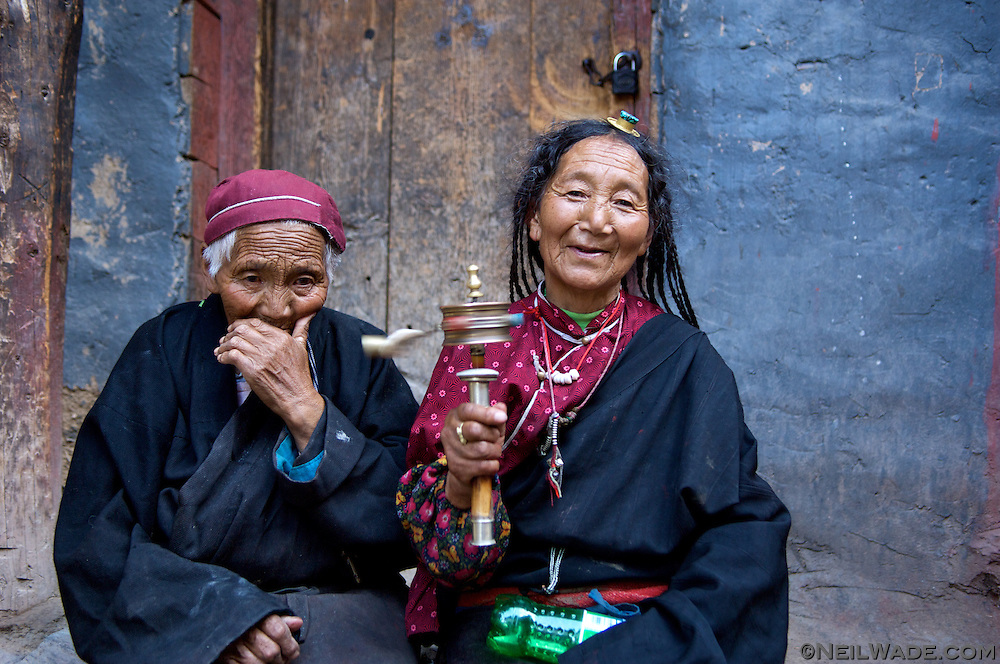 Two Tibetan women sit outside their home in Dege, Tibet.  The woman on the right is spinning a prayer wheel that brings good karma with every spin.  The woman on the left isn't coughing, she wanted her picture taken but she didin't want to show her teeth.