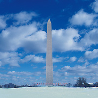 The Washington Monument in winter with snow on the ground and clouds above. Undated.