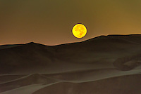 The full moon setting over the 750 foot tall sand dunes, Great Sand Dunes National Park and Preserve, near Mosca, Colorado USA.