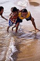 Kids swimming and playing on China Beach near Hoi An, Vietnam.