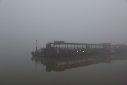 © Licensed to London News Pictures. 11/12/2013. London, UK. Tower Pier is seen shrouded in fog on 11 December 2013. Commuter riverboat services were cancelled this morning due to thick fog. Photo credit : Vickie Flores/LNP