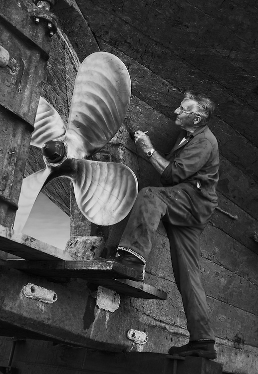 Roger Osborne, shipwright, working on PZ 425. <br /> <br /> Roger has been a shipwright for 25 years and at the time of the photograph was working for VSR Shipwrights.<br /> <br /> It is reputed that Newlyn's medieval 'Old Quay', still in existence, was the last port of call by the Pilgrim Fathers prior to their departure to America. This was probably in order to collect fresh water, as there was an outbreak of cholera in Plymouth.