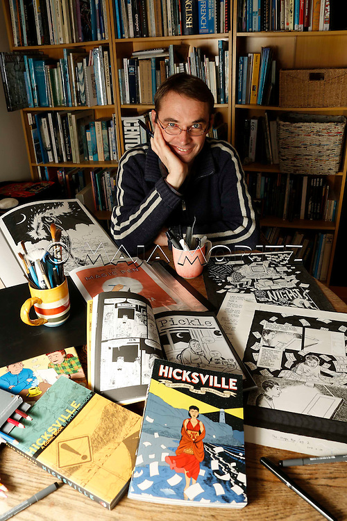 "Author and cartoonist Dylan Horrocks with his comic book ""Hicksville"" at home in Maraetai, Auckland, New Zealand"