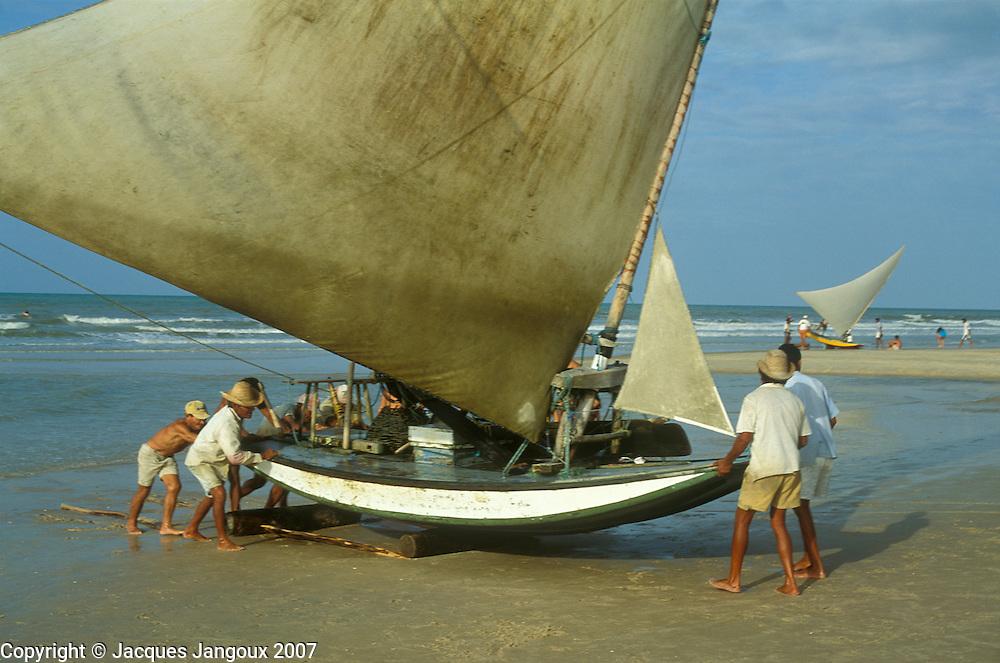Brazil, Ceara: fishermen pushing jangada (fishing raft) out of sea reach at Morro Branco Beach near Beberibe.