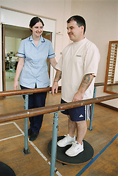 Rehabilitation session in hospital gym with patient working on balance with physiotherapy assistant,