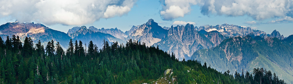 The Central Cascades form a wall as seen from Bald Mountain on the Walt Bailey Trail, in Mount Pilchuck Natural Resources Conservation Area (NRCA), accessed from the Mountain Loop Highway. Snohomish County, Washington, USA. Panorama stitched from 4 images.
