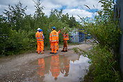 A group of men wearing high-visibility safety work clothing stand talking outside a shipping container yard depot in Aldershot, Hampshire, UK.  (photo by Andrew Aitchison / In pictures via Getty Images)