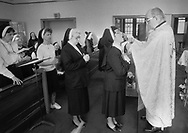 Father Basil Boysak (right) gives communion to Sister Marie Francis Wolchansky during morning mas at Sisters of Saint Basil The Great Tuesday May 1, 1990 in Jenkintown, Pennsylvania. Some of the sisters wear sneakers and blouses, a contradiction of stereotypes. (Photo by William Thomas Cain/Cain Images)