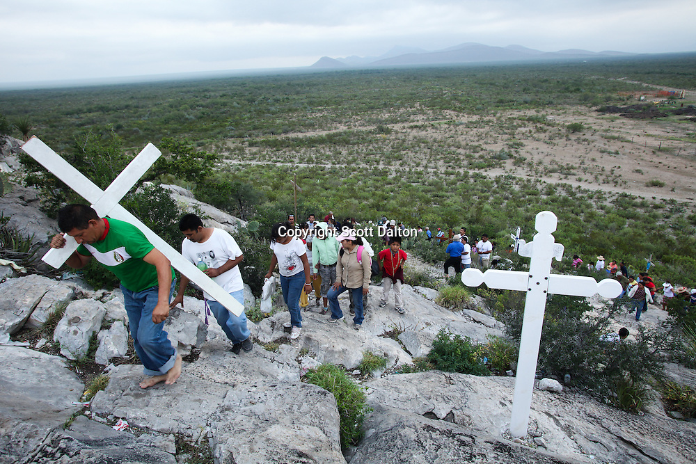 Followers of Nino Fidencio, a curandero or healer who passed away in the 1938, carry crosses to an early morning prayer and healing session on top of a hill just outside of Espinazo, Mexico on October 16, 2009. Followers of Nino Fidencio believe that his spirit can posses other healers, who once possessed speak in a child like voice and perform a variety of medical cures on their followers. His believers, an estimated 20,000, gather in his hometown for a three-day festival twice a year in March and October. (Photo/Scott Dalton).