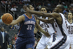 Apr 11; Newark, NJ, USA; Charlotte Bobcats power forward Boris Diaw (32) passes the ball around New Jersey Nets small forward Travis Outlaw (21) during the second half at the Prudential Center. The Bobcats defeated the Nets 105-103.